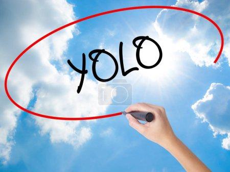 Photo pour Femme main écrit Yolo (vous Only Live Once) avec un marqueur noir sur écran visuel. Isolé sur le ciel ensoleillé. Concept d'affaires. Photo en stock - image libre de droit