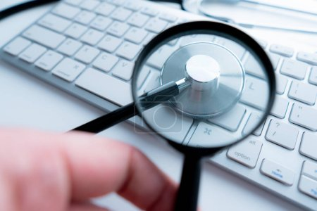 Magnifying glass lies on white keyboard on desk in office table workplace closeup.