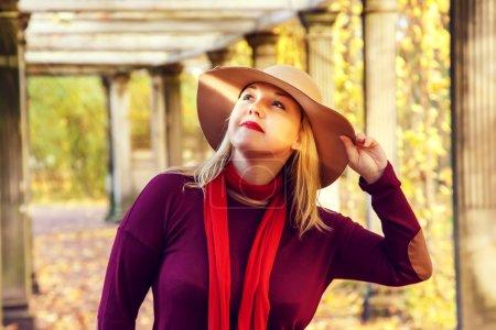 Photo pour Belle blonde dans un chapeau marchant dans le parc d'automne . - image libre de droit