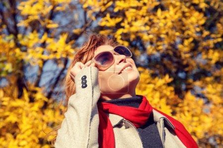 Photo pour Belle femme qui sent bon dans le parc d'automne. Vue du bas . - image libre de droit