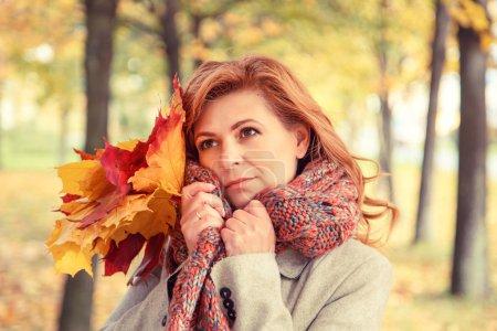 Photo pour Belle blonde dans un manteau marchant dans le parc d'automne . - image libre de droit