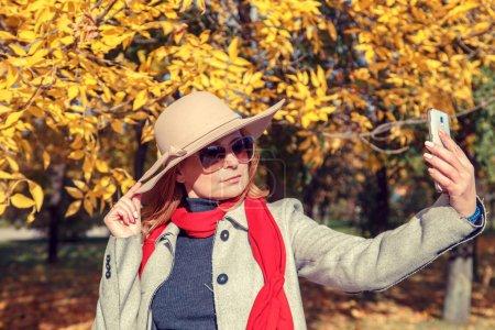 Photo pour Belle femme aux cheveux roux en chapeau faisant du selfie dans un parc d'automne . - image libre de droit