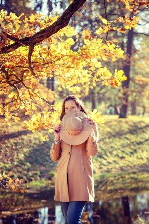 Photo pour Belle femme dans un chapeau marchant dans le parc d'automne . - image libre de droit