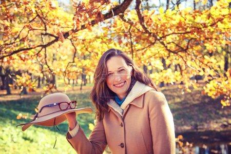 Photo pour Belle femme dans le parc jouant avec son chapeau . - image libre de droit
