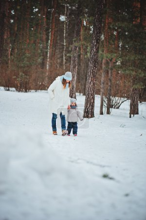 winter portrait of cute baby girl in oversize grey knitted scarf walking in snowy forest