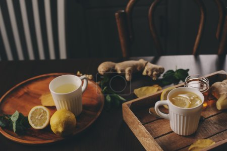 cooking ginger, lemon and honey hot tea in dark rustic interior. Ingredients and cup on wooden background