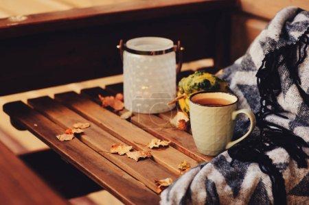Foto de Agradable mañana de otoño en la casa de campo, taza de té y manta en mesa de madera. Detalles de naturaleza muerta - Imagen libre de derechos