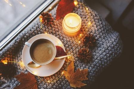 Foto de Invierno acogedor o mañana de otoño en casa. Café caliente con cuchara metálica oro, manta, luces guirnalda y vela, concepto hygge sueco. - Imagen libre de derechos