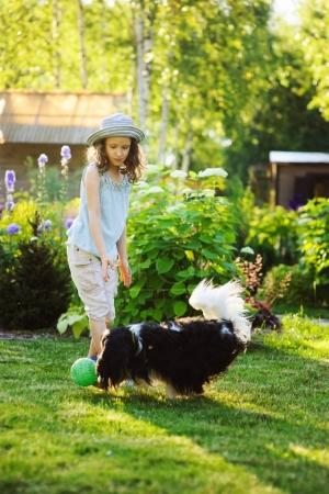 Photo for Happy child girl playing with her spaniel dog and throwing ball, enjoying sunny summer day in garden - Royalty Free Image
