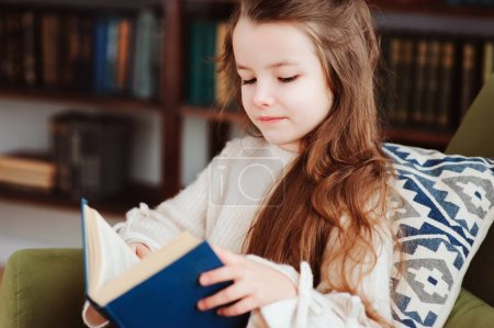 Photo for Happy smart schoolgirl reading books in library or at home. Kids early learning and education concept. - Royalty Free Image