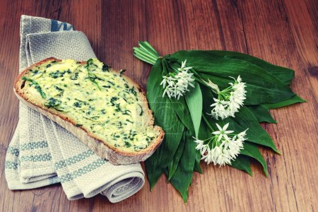 Photo for Bunch of wild garlic (ramson) and bread slice with ramson butter - Royalty Free Image