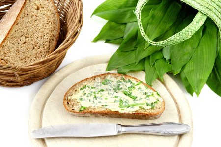 Photo for Bunch of wild garlic (ramson) and bread slice with ramson butter and antique silverware on isolated white background - Royalty Free Image