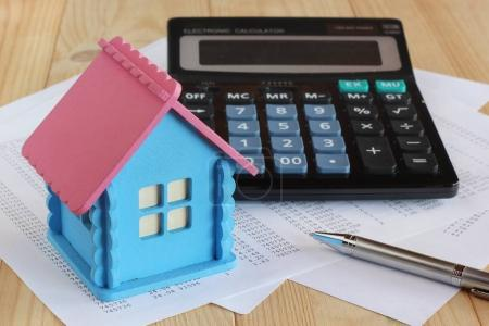 Electronic calculator with push buttons, wooden model house, met