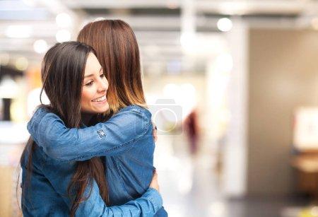 happy sisters hugging