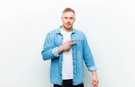 Photo pour Young blonde salope man wearing jeans shirt feeling happy, positive and successful, with hand making v shape over chest, showing victory or peace against white background - image libre de droit