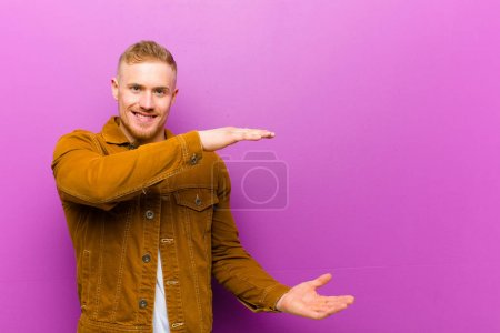 Photo for Young blonde man holding an object with both hands on side copy space, showing, offering or advertising an object against purple background - Royalty Free Image