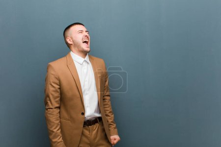 young handsome businessman screaming furiously, shouting aggressively, looking stressed and angry against flat background