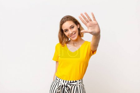 Photo for Young blonde woman smiling and looking friendly, showing number five or fifth with hand forward, counting down against flat color wall - Royalty Free Image