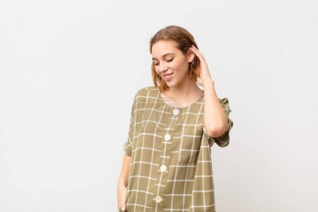 Photo for Young blonde woman smiling cheerfully and casually, taking hand to head with a positive, happy and confident look against flat color wall - Royalty Free Image