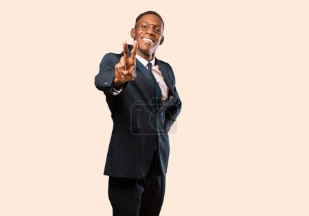 Foto de African American business man smiling and looking happy, carefree and positive, gesturing victory or peace with one hand against beige wall. - Imagen libre de derechos