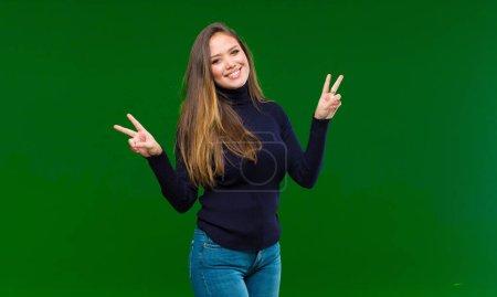 Photo pour Jeune jolie femme souriante et d'apparence joyeuse, amicale et satisfaite, jouant de la victoire ou de la paix avec les deux mains sur fond vert - image libre de droit