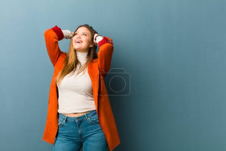 Foto de Joven mujer guapa sonriendo y sintiéndose relajada, satisfecha y sin preocupaciones, riendo positivamente y escalofriante. - Imagen libre de derechos