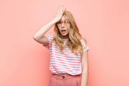 Photo pour Young pretty blonde woman raising palm to forehead thinking oops, after making a stupid mistake or remembering, feeling dumb against flat color wall - image libre de droit