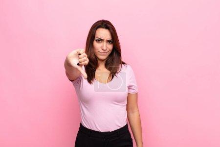 Photo pour Une jeune jolie femme se sentant en croix, en colère, contrariée, déçue ou mécontente, montrant les pouces en bas avec un regard sérieux contre le mur rose - image libre de droit