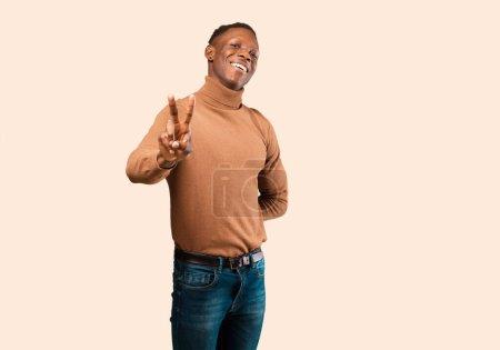 Photo pour Jeune afro-américain noir souriant et paraissant heureux, insouciant et positif, en signe de victoire ou de paix d'une main contre un mur beige - image libre de droit
