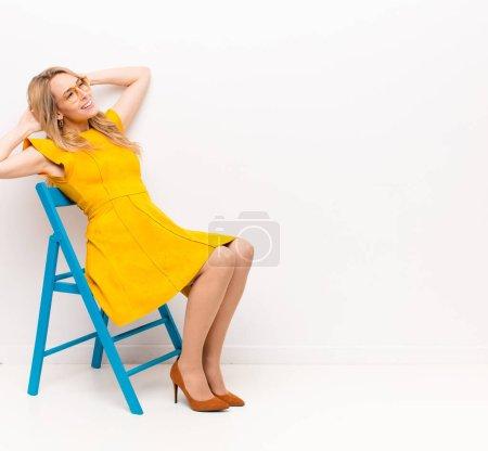 Foto de Jovencita rubia guapa que sonríe y se siente relajada, satisfecha y sin preocupaciones, reír positivamente y chupar contra la pared plana de color. - Imagen libre de derechos