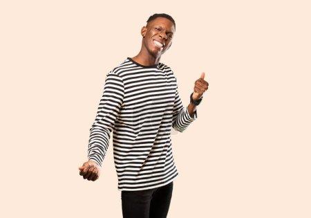 Foto de Jovencito negro africoamericano sonriendo, sintiéndose despreocupado, relajado y feliz, bailando y escuchando música, divirtiéndose en una fiesta contra la pared beige. - Imagen libre de derechos