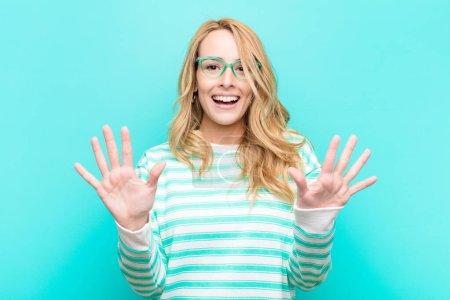 Foto de Jovencita rubia guapa que sonríe y se ve amistosa, mostrando el número diez o diez con la mano hacia delante, contando abajo contra la pared plana de color. - Imagen libre de derechos