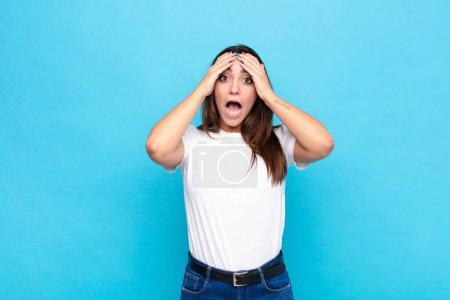 Photo pour Jeune jolie femme se sentant horrifiée et choquée, levant les mains à la tête et paniquant à une erreur contre le mur bleu - image libre de droit