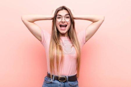 Foto de Jovencita mujer guapa que se ve feliz, sin preocupaciones, amistosa y relajada disfrutando de la vida y el éxito, con una actitud positiva contra la pared rosa. - Imagen libre de derechos