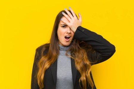 Photo pour Une jeune jolie femme se met à lever la paume de sa paume sur le front après avoir fait une erreur stupide ou s'être souvenue d'elle, d'un emploi stupide ou d'un concept d'entreprise - image libre de droit