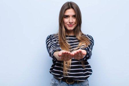 Foto de Joven mujer guapa sonriendo alegremente con un aspecto amistoso, seguro y positivo, ofreciendo y mostrando un objeto o concepto contra la pared azul suave. - Imagen libre de derechos