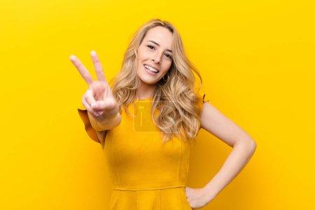Foto de Jovencita rubia guapa rubia sonriendo y luciendo feliz, despreocupada y positiva, gestuosa victoria o paz con una mano contra la pared plana de color. - Imagen libre de derechos