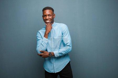 Foto de Jovencito negro africoamericano sonriendo con una expresión feliz y confiada con la mano en el mentón, preguntándose y mirando hacia el lado contra la pared gris. - Imagen libre de derechos
