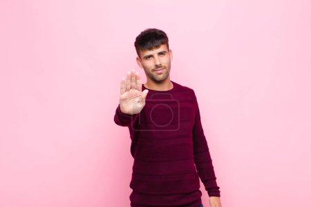 Photo pour Un jeune bel homme qui a l'air sérieux, sévère, mécontent et fâché en montrant sa paume ouverte en faisant un geste d'arrêt contre le mur rose - image libre de droit
