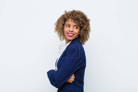 Photo for Young woman african american smiling gleefully, feeling happy, satisfied and relaxed, with crossed arms and looking to the side against flat wall - Royalty Free Image