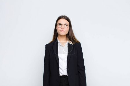 Young businesswoman looking puzzled and confused, ...