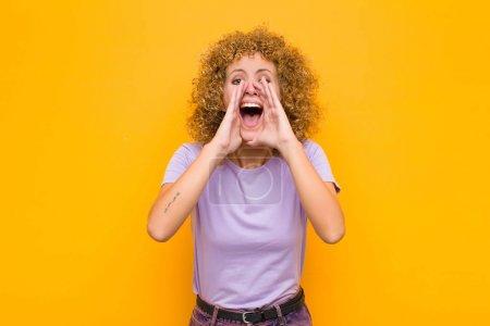 Photo pour Une jeune femme afro se sent heureuse, excitée et positive, crie avec les mains à côté de la bouche, crie contre le mur orange - image libre de droit