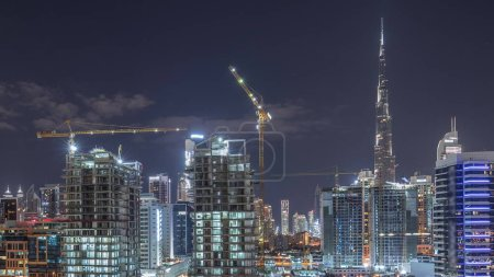 Photo for Skyline of the city at night with beautiful canal with reflections and bright skyscrapers aerial timelapse in Business Bay, Dubai, United Arab Emirates. Towers under construction - Royalty Free Image