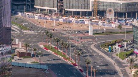 Photo pour Vue aérienne de la ville sur un carrefour à Dubaï Business bay timelapse. Jonction de la route d'en haut, circulation automobile et embouteillage de nombreuses voitures, mouvement du transport - image libre de droit
