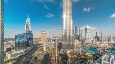 Photo for Panoramic skyline view of Dubai downtown with mall, fountains and Burj Khalifa aerial during all day timelapse with shadows moving fast. Modern skyscrapers and construction site. Cloudy blue sky - Royalty Free Image