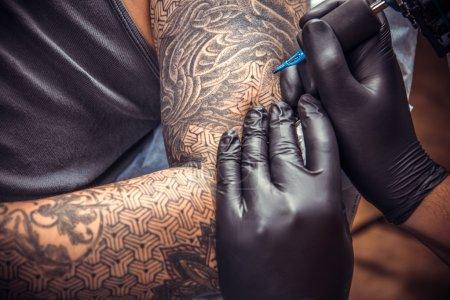Tattooer makes cool tattoo in tattoo studio