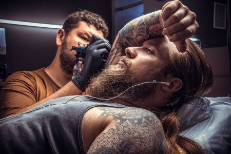 Professional tattooer create tattoo in studio