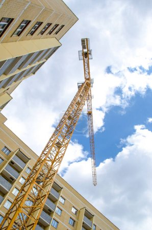 Multistorey houses under construction and big cranes