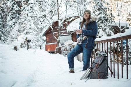Photo pour La fille aime les chutes de neige. Jeune femme vêtements chauds boit du thé dans la forêt pendant les chutes de neige - image libre de droit