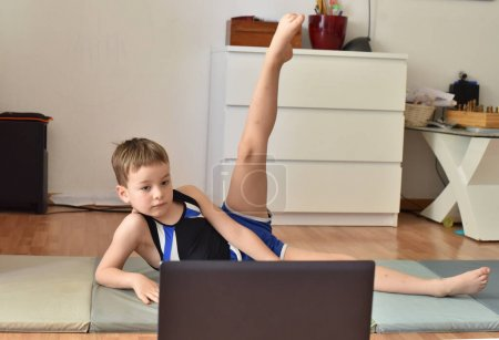 Little gymnast boy is training online with laptop ...